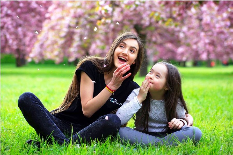 Therapist and young girl sitting in the park